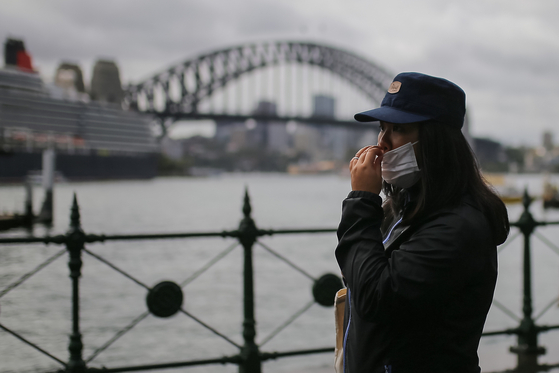 지난 3월 호주 시드니 하버브리지 앞에서 한 여성이 마스크를 쓴 채 걷고 있다.[EPA=연합뉴스]