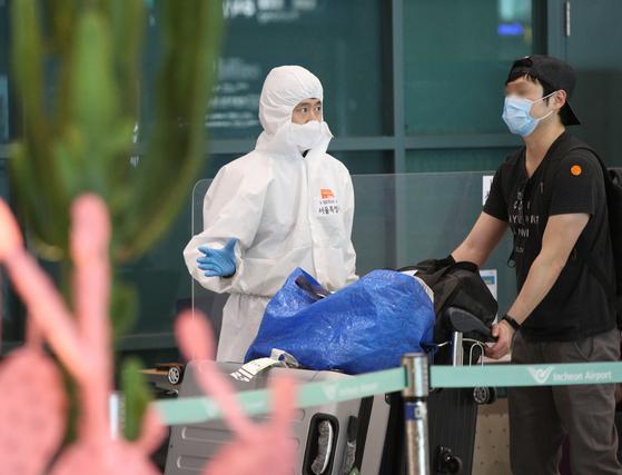 인천국제공항 입국장에서 검역 관계자들이 입국자들에게 안내를 하고 있다. 뉴스1