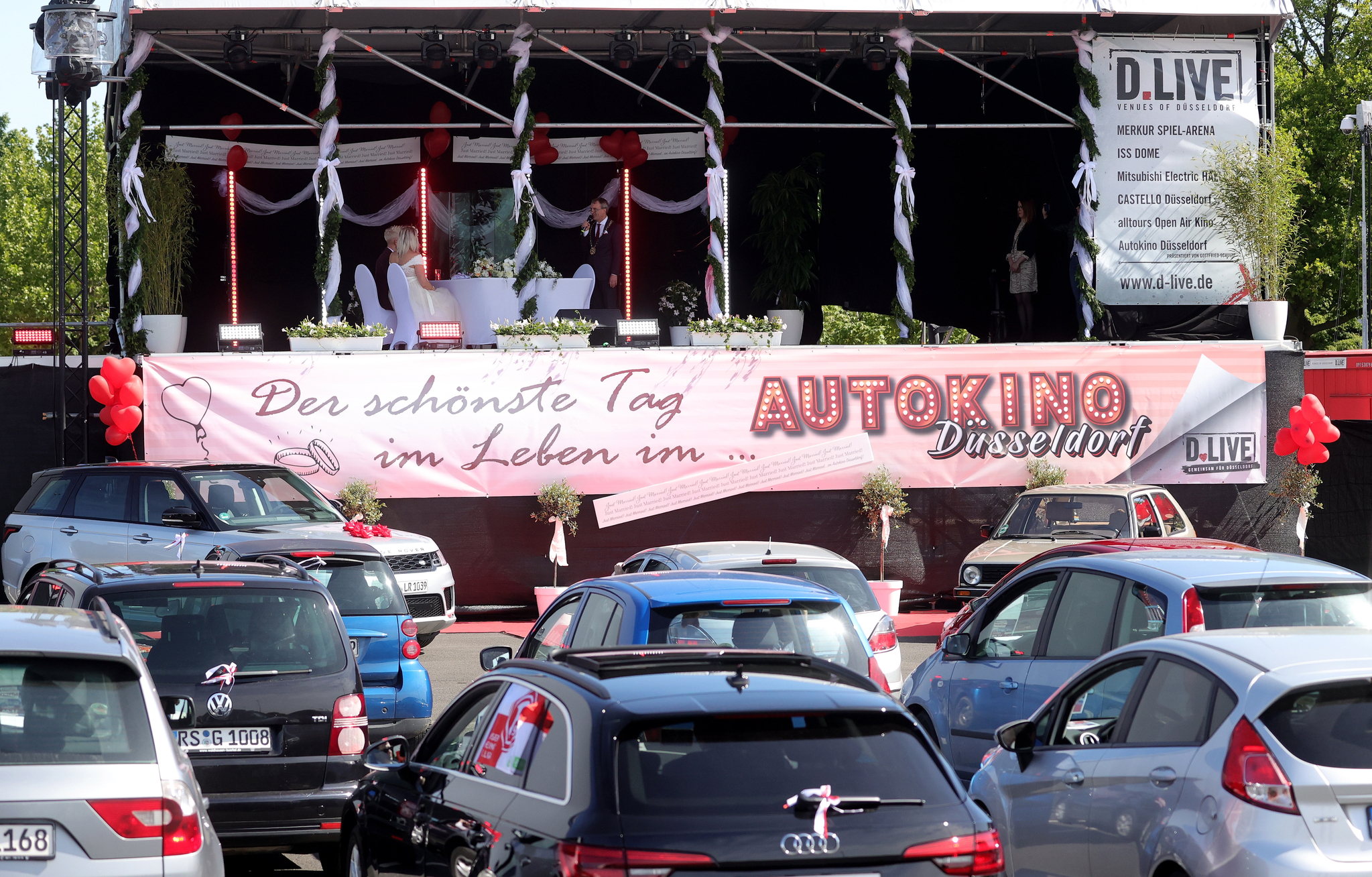 5일(현지시간) 독일 뒤셀도르프의 한 드라이브인 영화관 주차장에서 신부 재닌과 신랑 필립 스콜즈의 결혼식이 진행 되고 있다. 하객들이 자신의 차에 탄 채 결혼식을 지켜보고 있다. [EPA=연합뉴스]