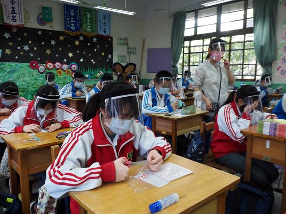 지난달 28일 대만의 한 중학교 수업시간에 아이들이 선생님의 지도를 받아 얼굴 보호막인 페이스실드를 직접 만들어 쓰고 있다. 역시 페이스실드와 마스크를 착용한 선생님은 아이들에게 자신의 목소리가 잘 들리도록 마이크를 사용해 수업하고 있다. [EPA=연합뉴스]
