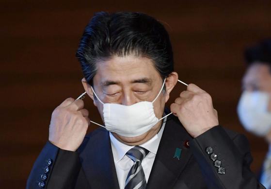 아베 신조 일본 총리가 지난 5월 1일 도쿄의 관저에서 기자회견을 앞두고 마스크를 벗고 있다. 아베 총리가 지난 4일 코로나 19로 인한 전국 긴급사태 시한을 6일에서 31일로 연장하면서 그간의 코로나 대응 행정과 리더십이 도마에 오르고 있다. 로이터=연합뉴스
