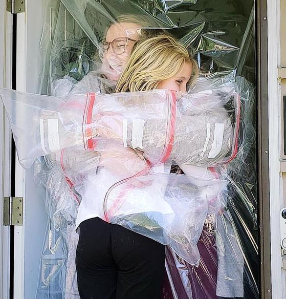 미국 인디애나 주 한 초등학교 교사 켈시 파벨카가 제자들을 집으로 초대해 비닐을 사이 두고 포옹하고 있다. 사진 켈시 파벨카 페이스북
