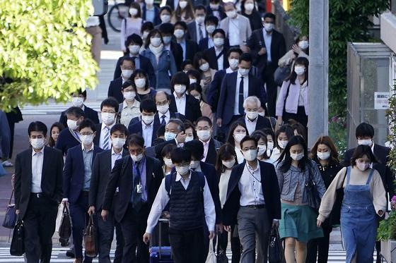아베 신조 일본 총리가 신종 코로나바이러스 감염증(코로나19) 대응을 위한 긴급사태 기간을 이달 말까지 연장한 이후 7일 도쿄 시민들이 마스크를 쓰고 출근길을 서두르고 있다. AP=연합뉴스