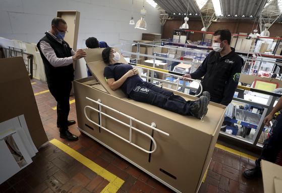 지난 8일 콜롬비아 보고타의 한 기업에서 제작한 '관으로 변하는 침대'의 사용 방법을 직원들이 시연하고 있다. 골판지로 만들어진 이 제품은 평소 병원 침대로 사용하다가 환자가 사망할 경우 침대 뚜껑을 열어 관으로 사용할 수 있다. 침대는 상반신을 위로 올려주는 기능과 금속 난간을 갖췄고, 무게 150kg까지 견딜 수 있다고 한다. [AP=연합뉴스]