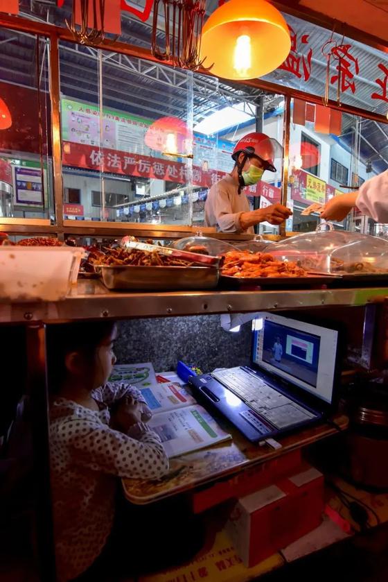 중국 후베이성 우펑현 위양관진의 한 시장 매대 아래에 차려진 공부방에서 온라인 수업에 몰두중인 초등학교 1년생 커언야. [중국 인민망 캡처]