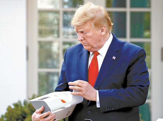도널드 트럼프 미국 대통령이 지난달 30일(현지시간) 백악관에서 브리핑 중 코로나 진단키트를 꺼내 살펴보는 모습. AP=연합뉴스