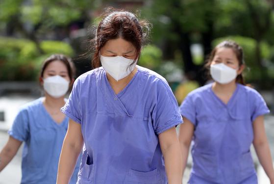 """12일 오후 신종 코로나바이러스 감염증(코로나19) 지역거점병원인 대구 중구 계명대 대구동산병원에서 중환자실 근무를 마친 간호사들이 격리병동을 나와 보호복을 벗고 지친 모습으로 휴게실로 향하고 있다. 오늘이 '국제 간호사의 날'인 것을 알고 있느냐는 취재진의 물음에 이들은 """"가정의 달 5월이지만 가족의 기념일도 잊은 지 오래됐다""""고 말했다. 뉴스1"""