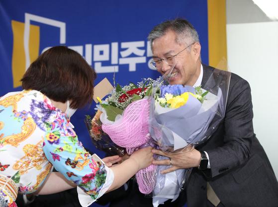 열린민주당 당대표로 선출된 최강욱 당선인이 12일 오전 서울 여의도 열린민주당사에서 열린 당대표 임명식에서 꽃다발을 전달받고 있다. [뉴스1]