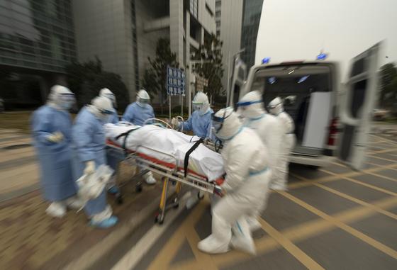 도시봉쇄가 해제된 지난달 9일 중국 후베이성 우한시에서 의료진이 코로나19 환자의 이송을 돕고 있다. [신화통신=연합뉴스]