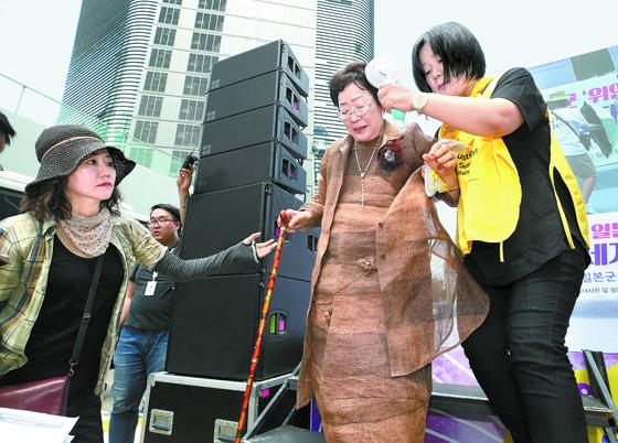 지난 2018년 서울 종로구 일본대사관 앞에서 열린 수요집회에 참석한 이용수 할머니(가운데)가 무대에서 내려오며 윤미향 더불어시민당 당선인(오른쪽)의 부축을 받고 있다. [연합뉴스]