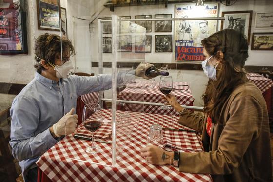 이탈리아 로마의 한 레스토랑 테이블에 투명 가림막이 설치돼 있다. 두 남녀가 이 가림막을 사이에 두고 앉아 와인을 마시고 있다. [EPA=연합뉴스]