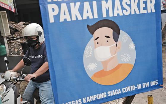 지난 12일 인도네시아의 자카르타 거리에 마스크 착용 의무화를 알리는 그림이 붙어있다. [AP= 연합뉴스]