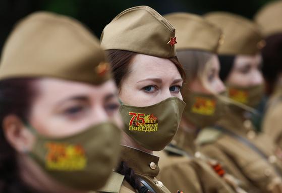 제2차 세계대전 유럽 전승기념일(VE)인 지난 9일 러시아 남부 볼고그라드(옛 스탈린그라드)의 추모 시설 앞에서 옛 소련 군복을 입은 여군들이 행사에 참석하고 있다. 코로나19 확산으로 75주년 전승기념일 표식이 찍힌 마스크를 착용하고 있다. 이날 공식행사는 연기됐으며, 최소한의 인원만 참석한 추모행사만 열렸다. 타스=연합뉴스