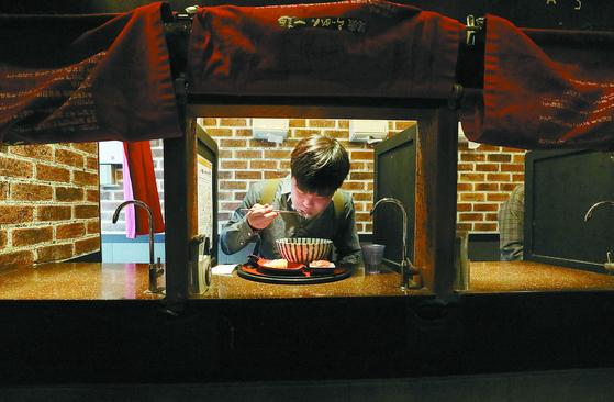 서울 신촌의 일본식라면 전문점 이찌멘의 1인전용 식사공간에서 한 시민이 식사를 하고 있다. 1인가구가 증가하며 '혼밥', '혼술'이 일반적인 문화가 됐다. 뉴스1