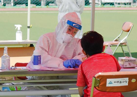 인천 학원강사 관련 신종 코로나바이러스 감염증(코로나19) 사태로 한 어린이가 미추홀구 관계자에게 검사를 받고 있다. 위 사진은 기사 내용과 무관. [사진 미추홀구]