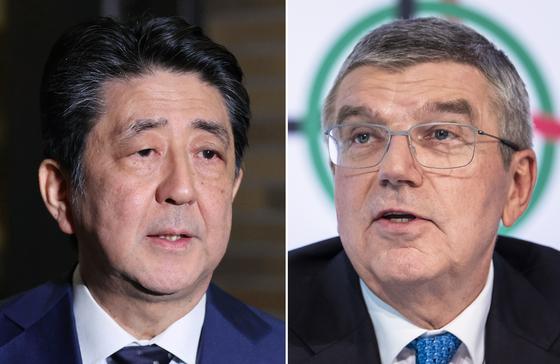 토마스 바흐 IOC 위원장(오른쪽)이 도쿄올림픽 연기에 따른 피해를 보상하기 위해 8억 달러를 지원하겠다고 밝혔다. 실제 피해 규모는 더 클 것으로 예상돼 일본 정부의 고민이 더 커질 전망이다. 사진 왼쪽은 아베 신조 일본 총리. [연합뉴스]
