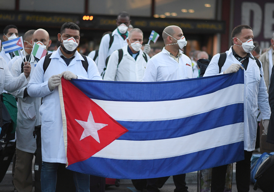쿠바 의료인력이 지난 3월 22일 로마의 레오나르도 다빈치 공항에 도착해 쿠바 국기를 내보이고 있다. 현재 이탈리아에는 80명의 쿠바 의료진이 일하고 있다. 로이터=연합뉴스