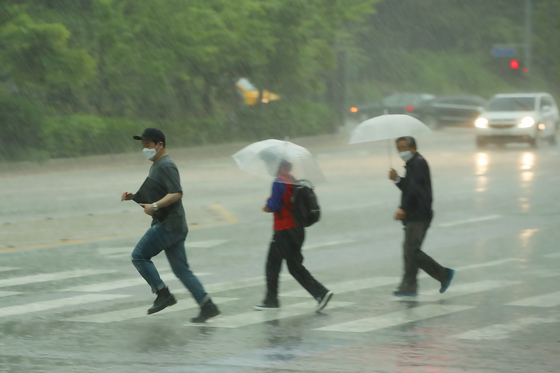 18일 오후 갑자기 내리는 폭우에 시민들이 황급히 이동하는 모습. 연합뉴스