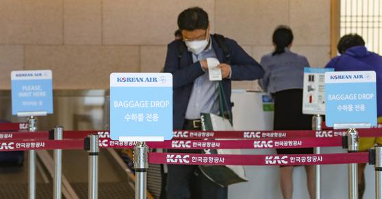 17일 서울 강서구 김포공항 국내선청사에 위치한 대한항공 체크인카운터 앞에서 마스크를 쓴 승객이 걸어가고 있다.   연합뉴스
