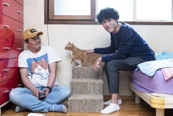 다큐멘터리 '고양이 집사'의 조은성 PD(왼쪽)와 이희섭 감독이 12일 서울 마포구 신수동 이 감독 자택에서 고양이 레니와 함께 포즈를 취하고 있다. 권혁재 사진전문기자