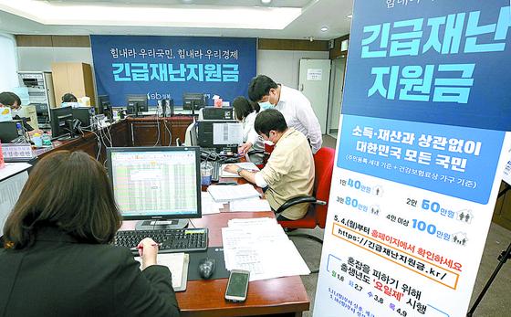 12일 서울 성북구청에서 직원들이 긴급재난지원금 신청과 관련해 안내와 상담을 하고 있다. 연합뉴스