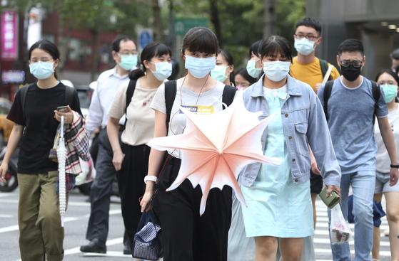 18일 대만 타이페이 시민들이 코로나19 예방을 위해 마스크를 착용한 채 거리를 걷고 있다. AP=연합뉴스