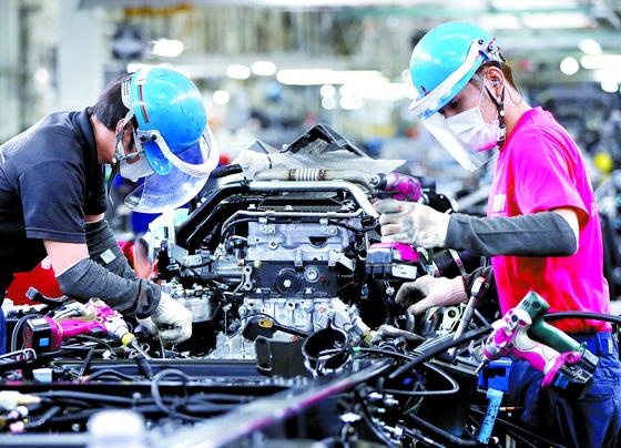 18일 일본 가와사키 미쓰비시 공장에서 얼굴 보호대를 쓰고 일하고 있는 노동자. [로이터=연합뉴스]