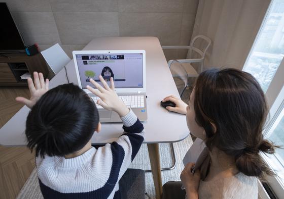 지난달 20일 오전 서울 용산구의 한 가정에서 용산초등학교 1학년에 입학한 신입생 어린이가 엄마와 함께 노트북 화면을 통해 온라인 입학식을 갖고 있다. 연합뉴스