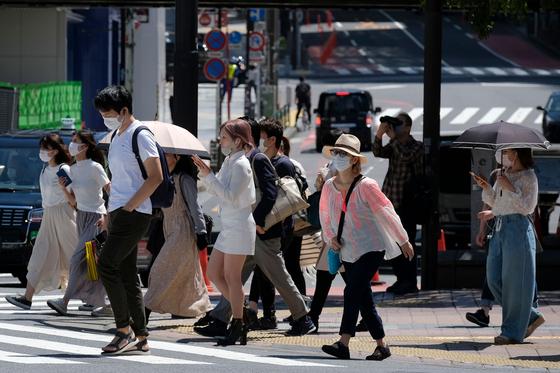 17일 이른 더위가 찾아온 일본 도쿄 시부야 거리를 마스크를 쓴 시민들이 지나고 있다. [AFP=연합뉴스]