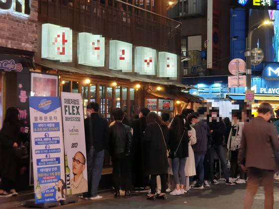 11일 새벽 서울 건대입구역 인근에 있는 헌팅포차에 20대로 보이는 이들이 줄 지어 서 있다. 중앙포토
