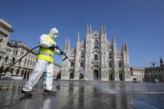 365일 관광객으로 북적이나 이탈리아 밀라노의 두오모 광장이 거짓말처럼 썰렁해졌다. 한 현지인이 광장을 소독하는 모습. [AP=연합뉴스]