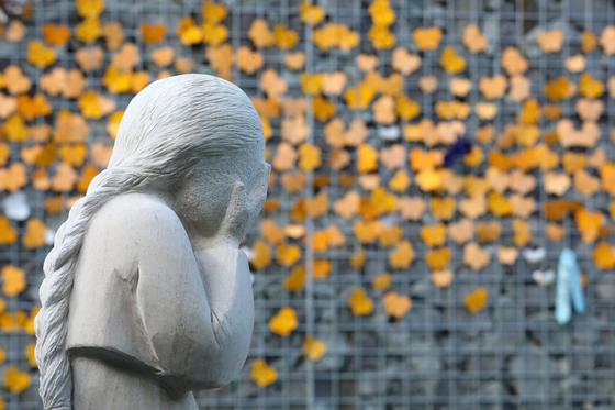 19일 오후 경기도 광주시 퇴촌면 나눔의 집 추모공원에 할머니들의 아픔을 표현한 작품 뒤로 시민들의 글귀가 적힌 노란 나비가 보이고 있다. 뉴스1