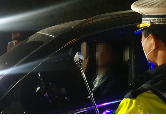 19일 오후 10시 서울 강서구 내발산동의 한 도로에서 이뤄진 비접촉 음주단속에서 경찰이 운전석에 감지기를 밀어넣고 음주운전 여부를 확인하고 있다. 정진호 기자