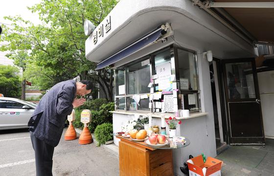 서울 강북구의 한 아파트에서 주민에게 지속적인 괴롭힘과 폭행을 당했다고 주장하는 경비원이 스스로 목숨을 끊는 사건이 발생했다. 11일 해당 아파트 경비실 앞에 차려진 분향소에서 한 주민이 애도하고 있다. 뉴스1