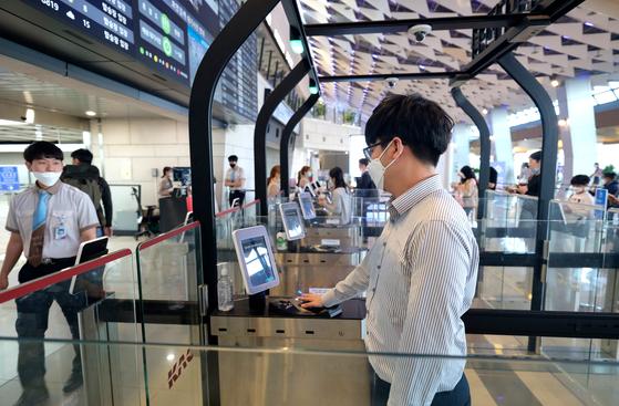 지난 18일 김포공항 이용객이 마스크를 쓴 채로 바이오 탑승 서비스를 이용해 출발장에 들어가고 있다. 곽재민 기자