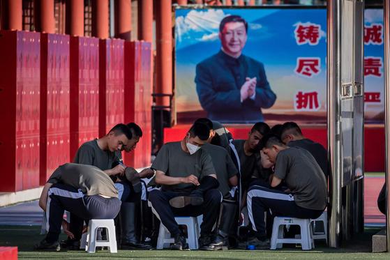 중국 인민 해방군 병사들이 19일 중국 자금성 입구 앞에서 구두를 닦고 있다. 뒤로는 시진핑 국가주석의 포스터가 보인다. AFP=연합뉴스]