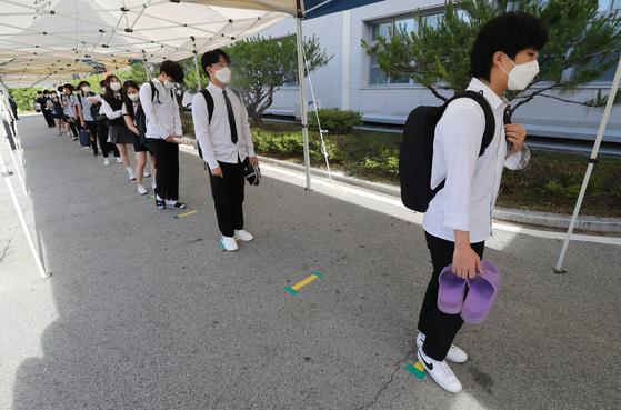 고등학교 3학년 등교 개학이 시작된 20일 오전 충북 청주시 상당구 금천고등학교에서 학생들이 체온 검사를 위해 거리를 두고 서 있다. 뉴스1