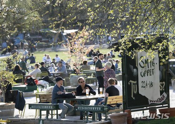 지난 달 22일 스웨덴 스톡홀름의 한 야외 술집에서 사람들이 모여 술을 마시고 있다. [AP=뉴시스]