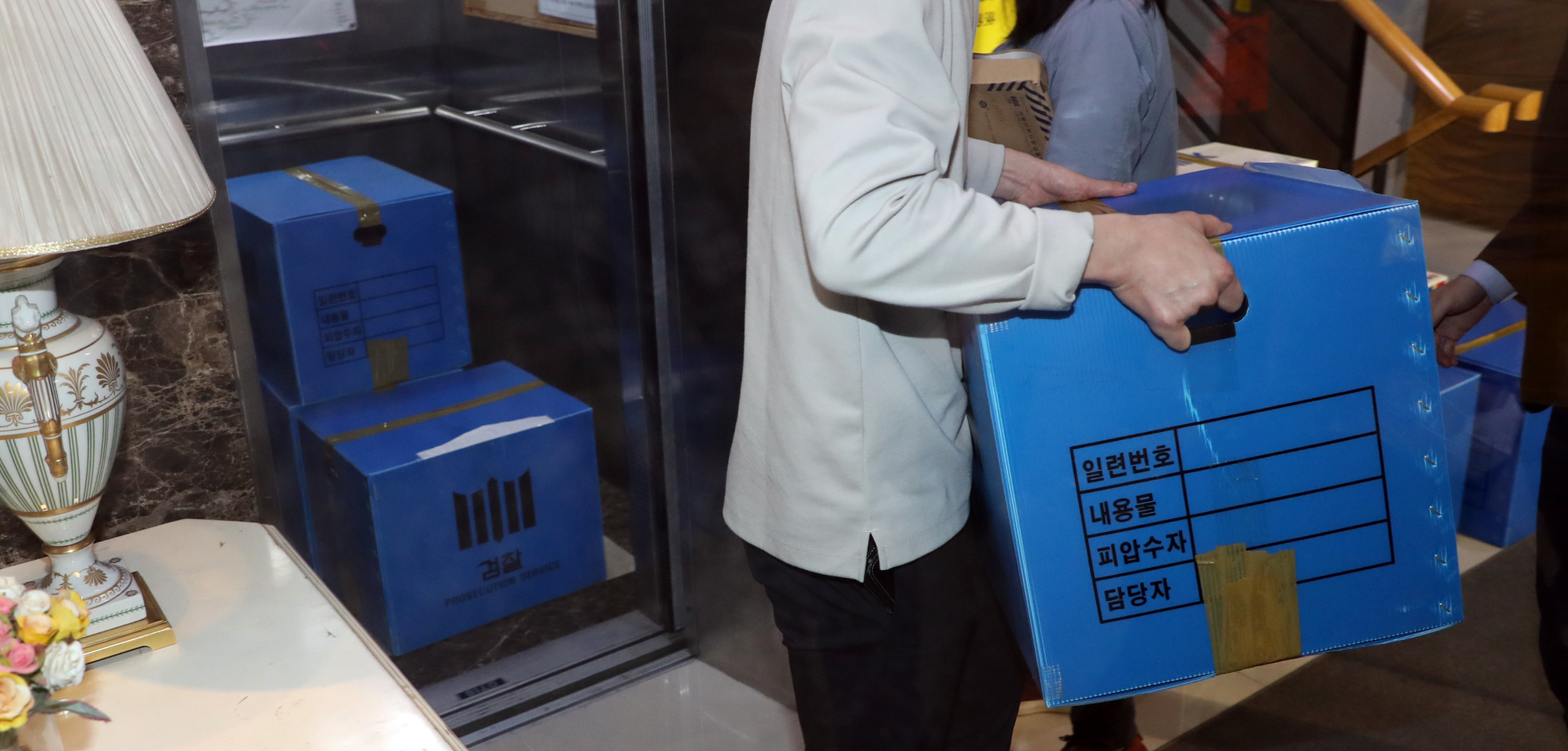 21일 마포구 정의기억연대 사무실에서 검찰이 압수수색 물품을 옮기고 있다. 검찰은 부실회계·안성 쉼터 고가 매입 의혹과 관련해 정의기억연대를 압수수색했다. 연합뉴스