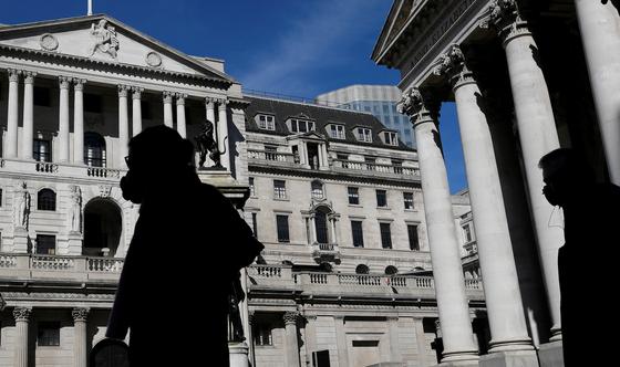 지난 3월 영국 영란은행(BOE) 앞에 마스크를 착용한 시민이 지나가고 있다. 영국은 코로나 사망자 세계 2위국에 오르며 방역에 실패했다는 평가를 받고 있다. [로이터=연합뉴스]