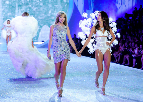 2013년 빅토리아 시크릿의 연말 패션쇼, 가수 테일러 스위프트가 모델 릴리 앨드리지와 함께 런웨이를 걷고 있다. [AP=연합뉴스]