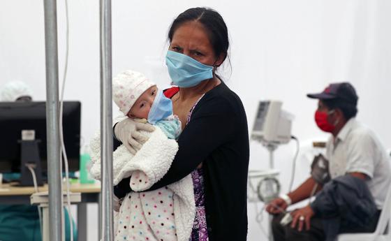 지난 20일 에콰도르의 한 병원에서 아기를 안은 여성이 진료를 기다리고 있다. 어린이의 경우 코로나19 감염이 잘 일어나지 않고, 일어나더라도 증세가 심하지 않다는 보고가 많다. AP=연합
