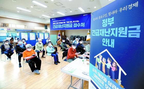 긴급재난지원금 오프라인 신청 접수 첫날인 지난 18일 서울 종로구 청운효자동 주민센터에서 시민들이 지원금 접수를 기다리고 있다. 연합뉴스