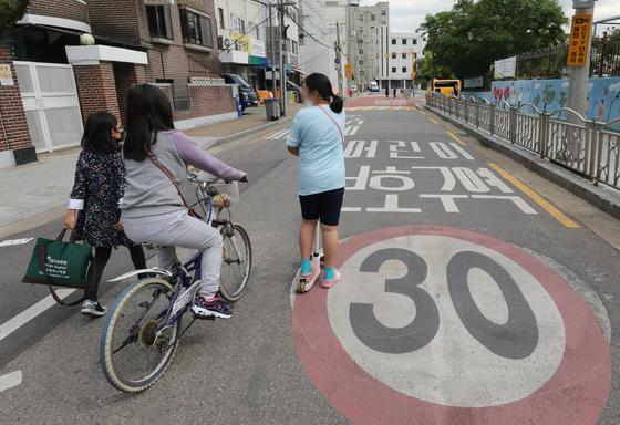 '민식이법' 시행 후 순차 등교가 시작된 20일 서울 영등포구 한 초등학교 앞에서 어린이들이 어린이보호구역 일대를 지나고 있다. 뉴스1