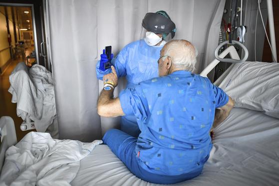 지난달 3일 이탈리아의 한 병원에서 의료진이 휴대폰을 들어보이며 코로나19 환자의 화상 통화를 돕고 있다. AP=연합