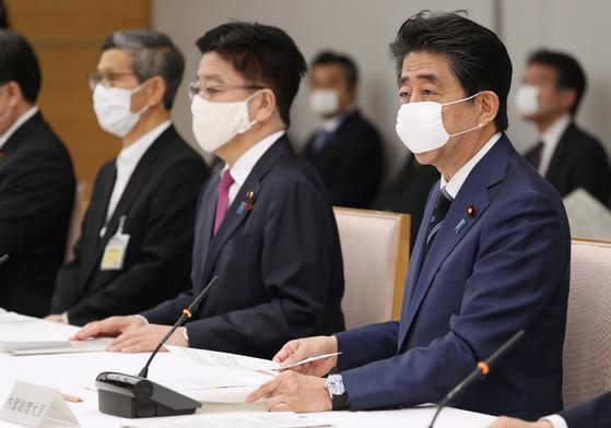 아베 신조 (오른쪽) 일본 총리가 지난 21일 총리관저에서 코로나19 정부대책본부 회의에 참석해 발언하고 있다. [지지통신=연합뉴스]