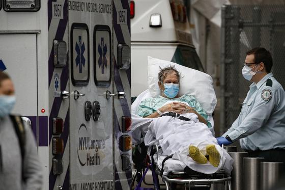 지난달 13일 미국 뉴욕시의 한 병원 응급실에서 노인 환자를 옮기고 있다. 노인 환자나 기저질환이 있는 일부 환자의 경우 코로나19 증세가 심각한 상황에 이르기도 한다. AP=연합