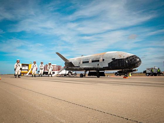 2014년 10월 674일간의 임무를 마치고 지구로 귀환한 X-37을 미국 공군 대원들이 점검하고 있다. 우주에서 온 각종 오염물질로부터 보호하기 위해 공군 대원들은 특수 보호복을 입었다. [보잉]