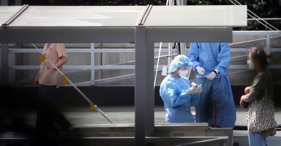 21일 오전 강남구 삼성서울병원 야외주차장 옥상에 차려진 코로나19 검사소에서 의료진을 비롯한 병원 관계자 등이 검사를 진행하고 있다. [연합]