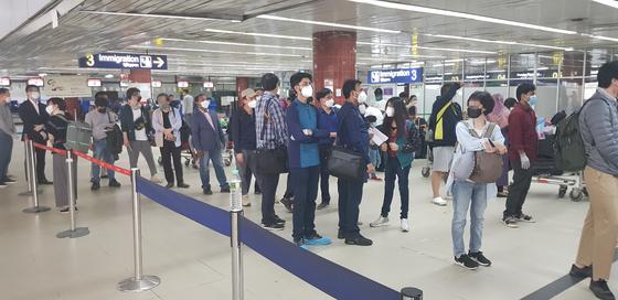 방글라데시 교민 140명이 현지시간 11일 오후 9시20분 대한항공 2차 전세기 편으로 다카 하즈라트 샤잘랄 국제공항에서 귀국길에 올랐다. 이들은 현지 신종 코로나바이러스 감염증(코로나19) 확산을 우려해 귀국을 결정했으며 공항에서는 대사관 직원 4명이 출국 수속 등을 지원했다.  사진은 교민들이 출국 수속을 밟고 있는 모습. [연합]